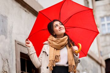 Woman with red umbrella walking in the old town.