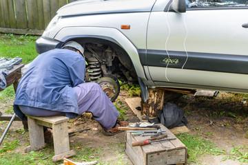 Senior mechanic repairing the front hub wheels.