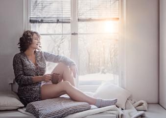 woman sitting beside window in the winter morning sun relaxing