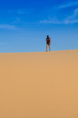 Female photographer with her backpack travelling in windy white sand dunes at Muine desert, Phan thiet, Vietnam