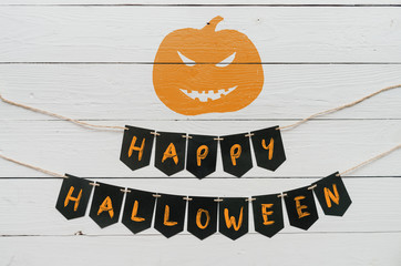Handwritten happy halloween banner lettering, cut pumpkin on white rustic painted barn wood background