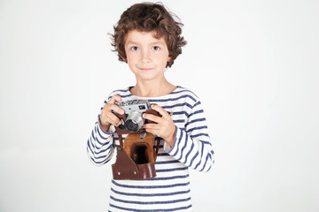 Cheerful smiling child (boy) holding a film camera