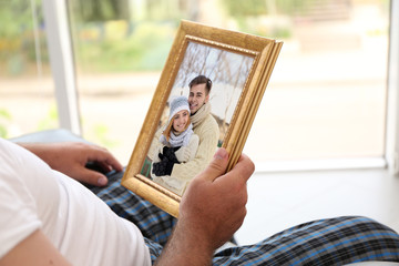 Male hands holding photo frame with picture of young couple. Happy memories concept.