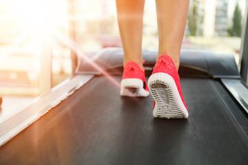 Legs of sporty woman running on treadmill in gym, close up view