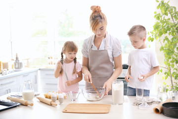 Mother and kids making dough in kitchen
