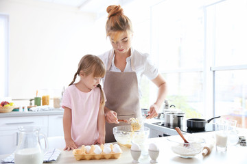 Mother and daughter making dough in kitchen