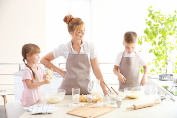 Young mother and kids making dough in kitchen