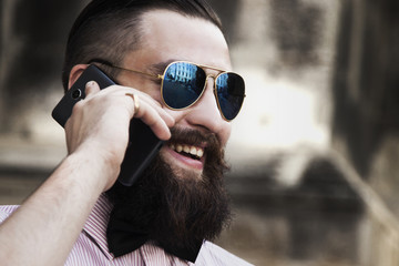 young hipster businessman with beard in sunglasses talking phone