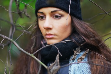 Beautiful pensive woman with brown eyes wearing a scarf and  hat in the Park among the bare branches of trees