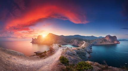 Wall Mural - Amazing summer landscape with mountains, sea, blue sky, sun and beautiful colorful red clouds at sunset in Crimea. Sunset in mountains. Panoramic. Nature background. Vibrant landscape in twilight.