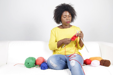 African woman knitting, sitting on a white couch. Surrounded by balls of yarn, she is knitting something with red colour.