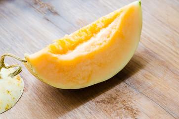 Fresh sliced cantaloupe on wooden background