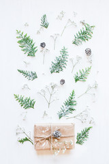 Christmas gift, pine cones, thuja branches and gypsophila flowers. Top view, flat lay