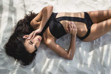 Beautiful girl in a sexy black swimsuit in paradise