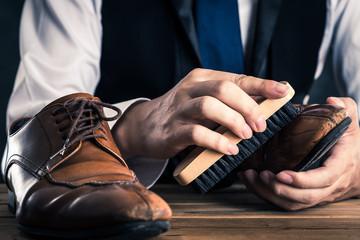 革靴の手入れをする男性