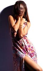 Beautiful sunbathed girl model in summer colorful dress with bright creative makeup posing near white wall