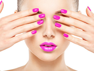 Close-up face of a beautiful  girl with  purple nails and lips.