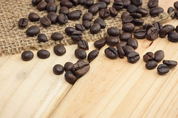 Coffee beans on sackcloth and wood background.