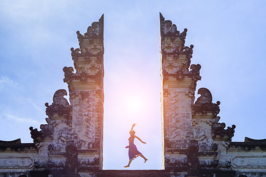 Woman traveler jumping with energy in gate temple, Bali, Indonesia