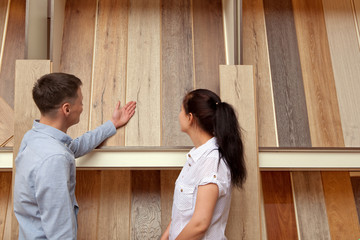 Couple looking at parquet board for home flooring in store