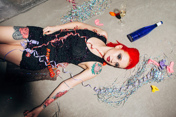 Hooked tattooed red haired woman in black dress lies on the dirty ground. Drug addiction in modern society.
