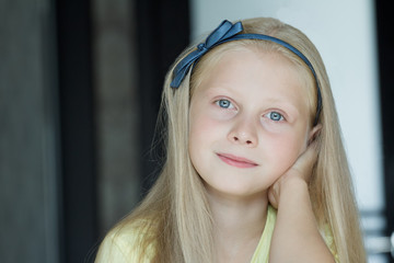 Head and shoulders indoor portrait of teenage girl with blue eyes and fair hair