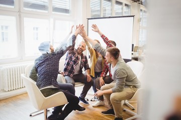 Creative business people giving high-five in meeting room