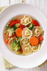 Italian soup with tortellini and vegetables closeup at the plate. vertical top view