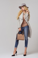 Poster Ranch Fashion blonde model in nice clothes posing in the studio. Wearing coat, hat, handbag, ripped jeans