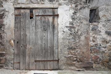 Vieille porte en bois d'une grange de village en montagne