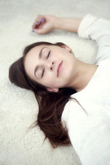 portrait of young woman sleeping on carpet