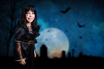 kleines Mädchen als Hexe verkleidet vor Hintergrund mit vielen Fledermäusen