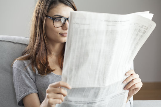 Young woman reading newspaper