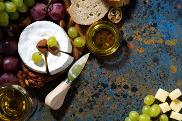 snacks and camembert and dark background, top view closeup