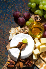 snacks and camembert on dark background, top view vertical