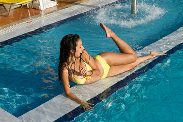 Beautiful brunette woman relaxing on wet marble in the pool.