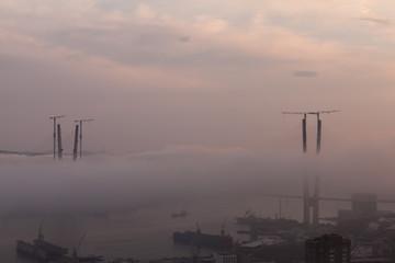 Vladivostok cityscape. Foggy day. Construction of the bridge.