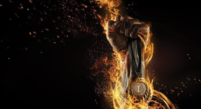 Sport. Man's hand holding up trophy medal. Winner in a competition. Fire and energy