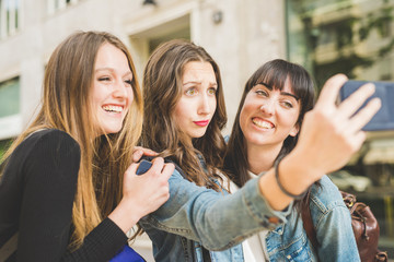 three beautiful young women taking selfie