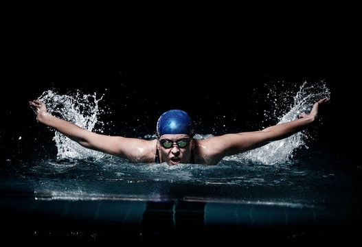 Profesional woman swimmer swim using breaststroke technique on the dark background