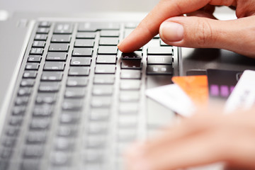 Business woman at notebook making online payments with credit cards