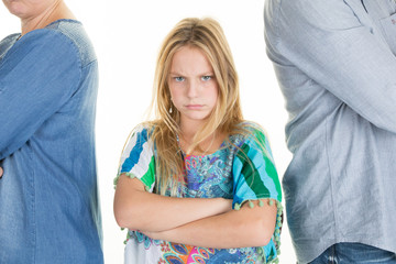 Unhappy girl standing between divorcing father and mother