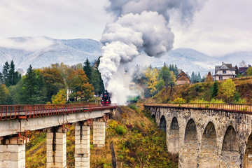 Old steam train passing over railway viaduct in Carpathian mountains, colorful countryside landscape
