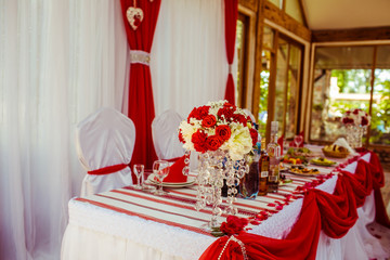 White dinner table decorated with red cloth and bouquets
