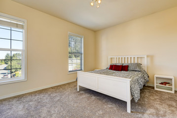 Simple upstairs bedroom with soft peach walls, gray carpet
