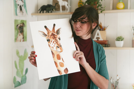 Portrait of artist showing her aquarelle of a giraffe