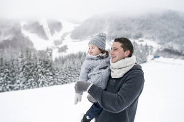 Father holding daughter in winter landscape