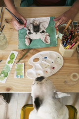 Woman's hand painting an aquarelle of French bulldog