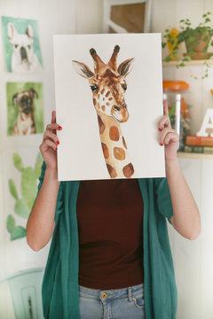 Artist hiding behind aquarelle of a giraffe