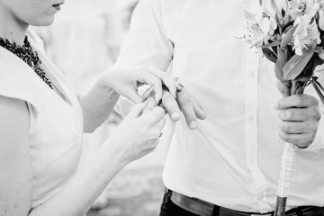 Black and white picture of bride adjusting a ring on groom's fin